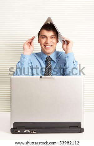 Portrait of happy businessman at workplace looking at camera with laptop in front