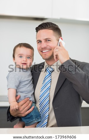 Portrait of happy businessman carrying baby boy while on call at home - stock photo