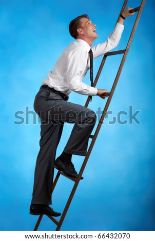 Portrait of happy businessman climbing staircase over blue background - stock photo