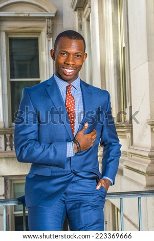 Portrait of Happy Businessman. Dressing formally in blue suit, patterned under shit, neck tie, a hand resting on chest, a young professional standing in office building, smiling, looking at you.