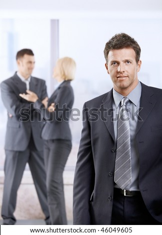 Portrait of happy businessman in office lobby, smiling. Colleagues talking in the background. - stock photo