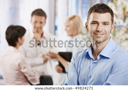 Portrait of happy businessman in office, smiling. Colleagues talking in the background. - stock photo