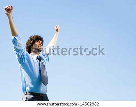 Portrait of happy businessman lifting up hands on the background the sky - stock photo