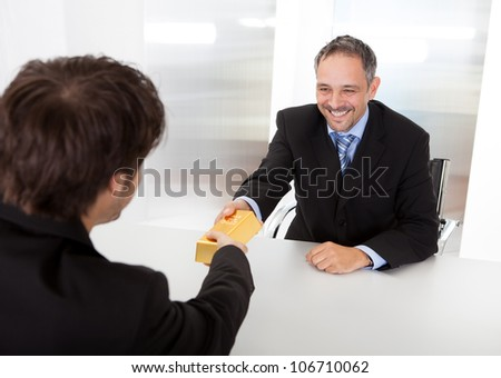 Portrait of happy businessman receiving gold bar - stock photo