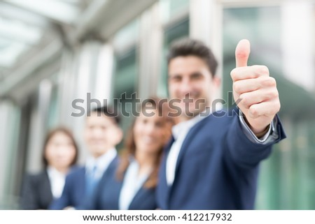 Portrait of happy businessman smiles and showing thumb up sign in office - stock photo