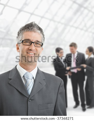 Portrait of happy businessman standing  in office hallway, smiling.