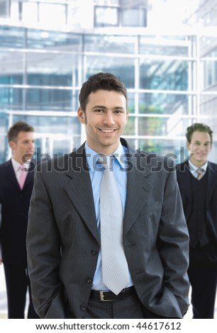 Portrait of happy businessman standing in office lobby, smiling. - stock photo