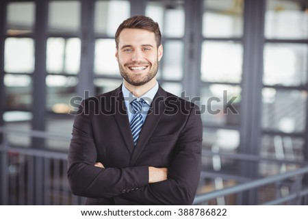 Portrait of happy businessman with arms crossed standing in office - stock photo