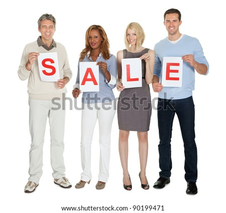 Portrait of happy businesspeople holding white paper with word sale on white background - stock photo