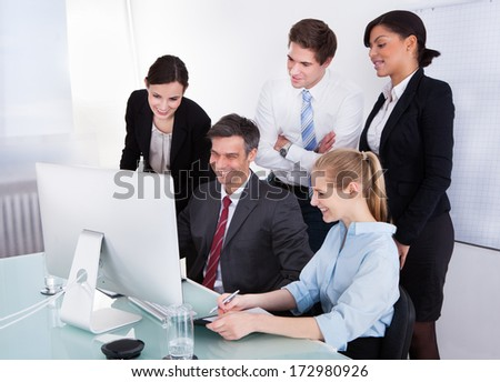 Portrait Of Happy Businesspeople In Office Looking At Computer