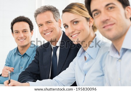 Portrait Of Happy Businesspeople Looking At Camera Sitting In A Row At Office - stock photo
