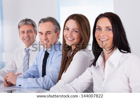 Portrait Of Happy Businesspeople Sitting In A Row - stock photo