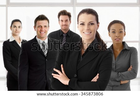 Portrait of happy businesswoman and business team looking at camera, smiling. - stock photo
