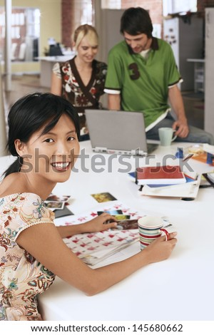 Portrait of happy businesswoman at table with colleagues using laptop in background - stock photo