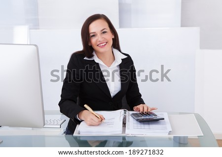 Portrait of happy businesswoman calculating tax at desk in office - stock photo
