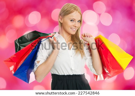 Portrait of happy businesswoman carrying shopping bags against colored background - stock photo
