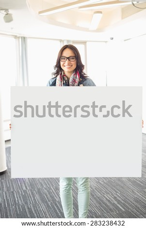 Portrait of happy businesswoman holding blank sign in creative office - stock photo