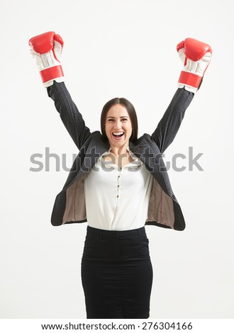 portrait of happy businesswoman in formal wear and red boxing gloves looking at camera over light grey background - stock photo