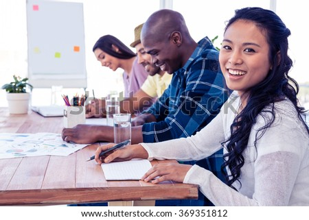 Portrait of happy businesswoman sitting with colleagues in conference room - stock photo