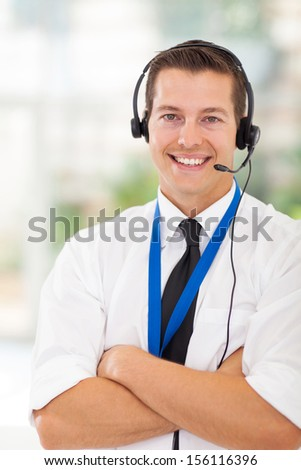 portrait of happy call center customer service worker with arms crossed - stock photo