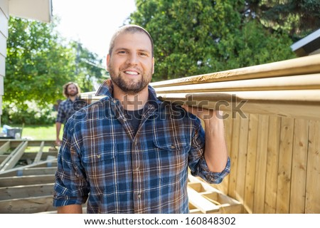 Portrait of happy carpenter and coworker carrying lumbers on shoulders at construction site - stock photo