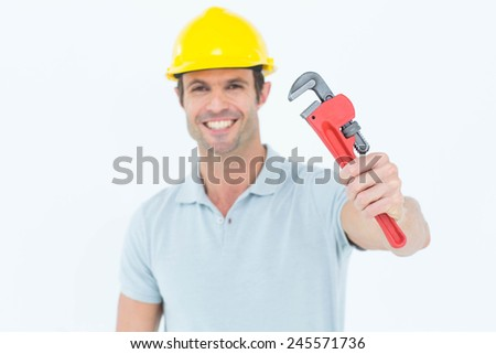 Portrait of happy carpenter holding monkey wrench over white background