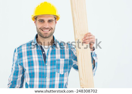 Portrait of happy carpenter holding wooden plank against white background - stock photo