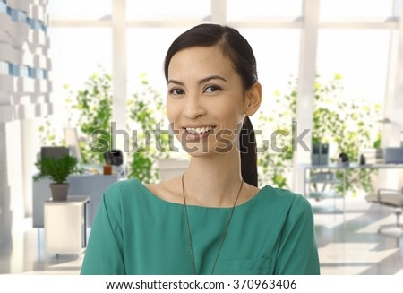 Portrait of happy casual asian businesswoman at office. Looking at camera, smiling. Copyspace. - stock photo