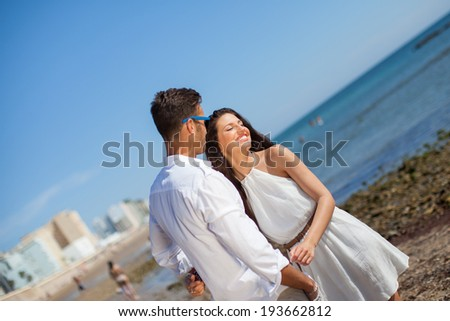 Portrait of happy casual caucasian married couple at the beach.