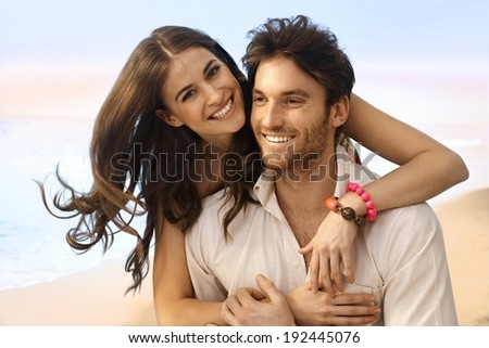 Portrait of happy casual caucasian married couple at the beach. Handsome man, attractive young woman, smiling, looking at camera, embracing. - stock photo