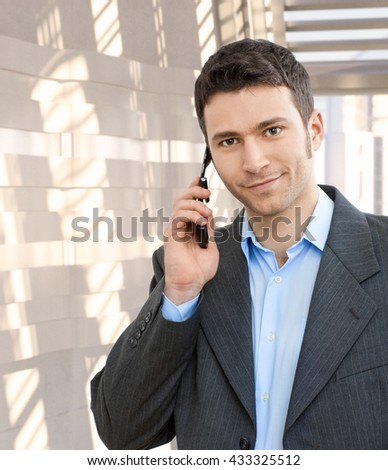 Portrait of happy caucasian businessman using mobile phone. Smiling, looking at camera, suit no tie. - stock photo
