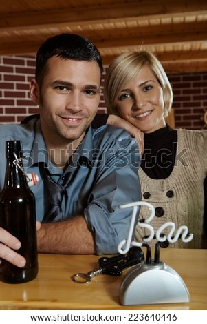 Portrait of happy caucasian couple having a drink at bar counter. Smiling, looking at camera. - stock photo