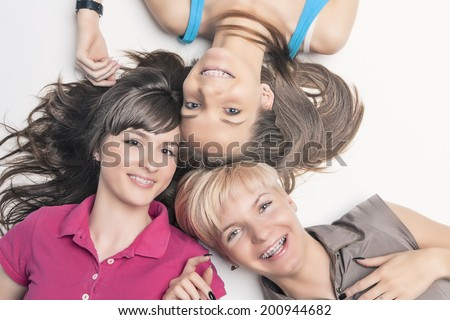 Portrait of Happy Caucasian Girls Wearing Teeth Braces Lying Together with Heads In Center. Horizontal Image