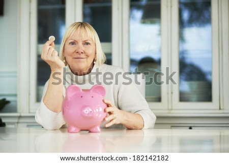 portrait of happy caucasian senior woman saving euro coin into piggybank and smiling at camera - stock photo