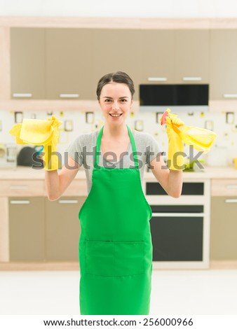 portrait of happy caucasian woman standing in kitchen and holding cleaning products - stock photo