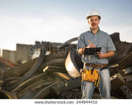 portrait of happy caucasian worker standing in metal landfill outdoors, writing - stock photo
