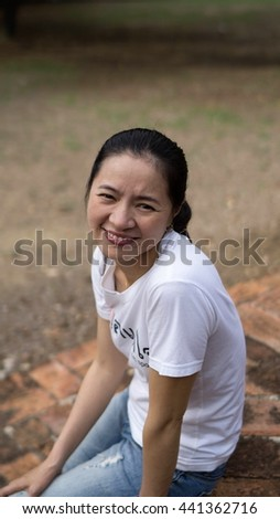 "Portrait of happy charming Vietnamese woman reading a book outdoors,A portrait of  asian woman smiling brightly at the camera, Non-English message on t-shirt says """"I am Self-willed"" In Thai language. - stock photo"