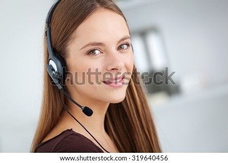 Portrait of happy cheerful beautiful young support phone operator with headset. - stock photo