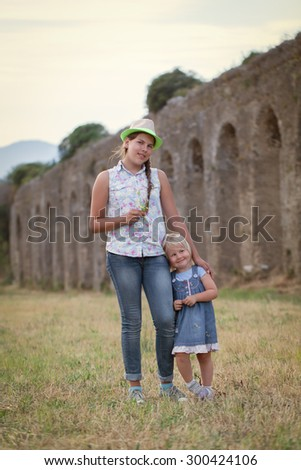 Portrait of happy cheerful sisters on background of old aqueduct (ruins), outdoor - stock photo