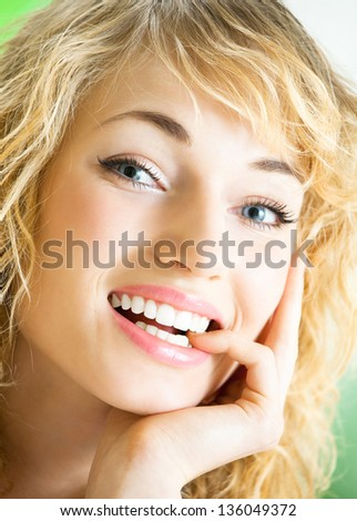 Portrait of happy cheerful smiling thinking young beautiful blond woman, indoors - stock photo