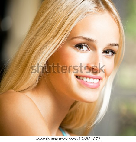Portrait of happy cheerful smiling young beautiful blond woman, indoors