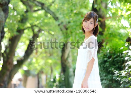 Portrait of happy cheerful smiling young beautiful japanese woman outdoors - stock photo