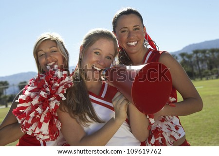 Portrait of happy cheerleader holding megaphone with friends - stock photo