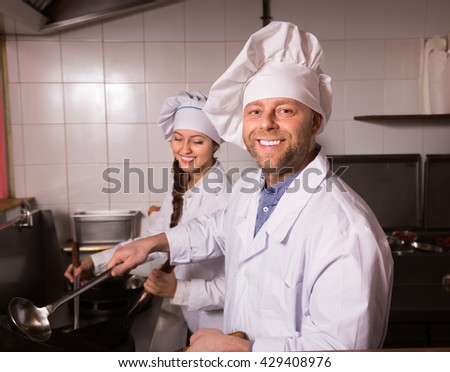 Portrait of happy chef with beautiful smiling young female assistant at kitchen in cafe