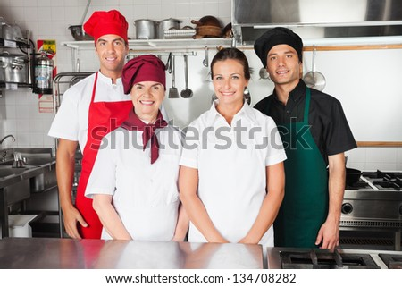 Portrait of happy chefs standing together in commercial kitchen
