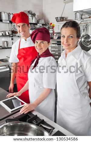 Portrait of happy chefs with digital tablet in commercial kitchen - stock photo