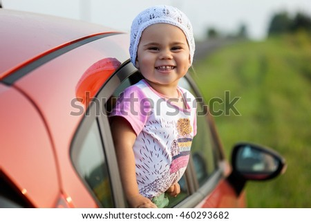 Portrait of happy child girl sticking their head out the car window. Concept of road trip