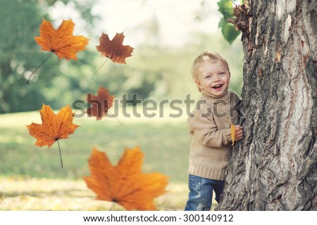Portrait of happy child playing having fun in warm autumn day with flying yellow maple leaves - stock photo