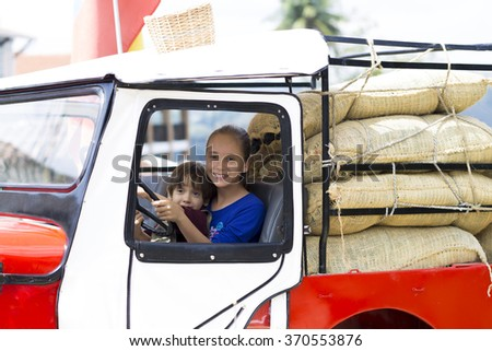 Portrait of Happy Children in Old Car Having Fun Outdoors - stock photo