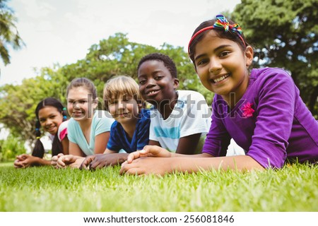 Portrait of happy children lying on grass at the park - stock photo